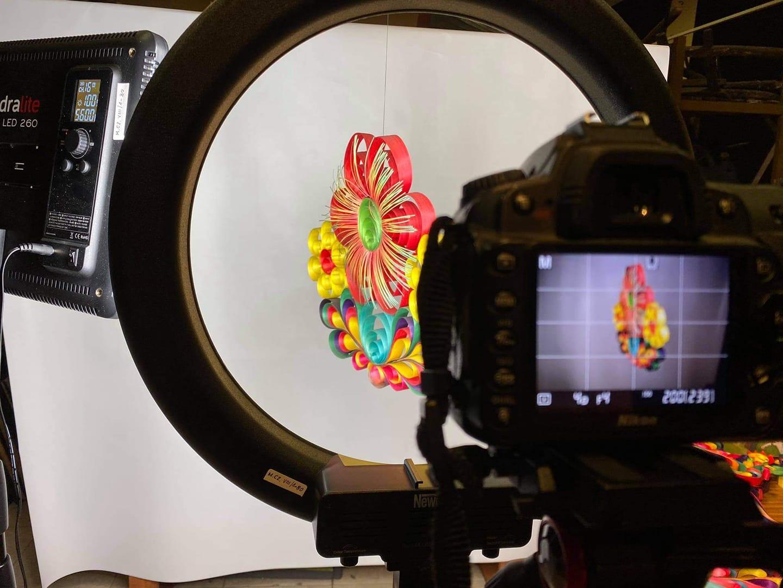 Ozdoba z wiórów osikowych podczas sesji fotograficznej. Nazdjeciu widoczne - aparat, lampy oraz kolorowy kwiat z osiki