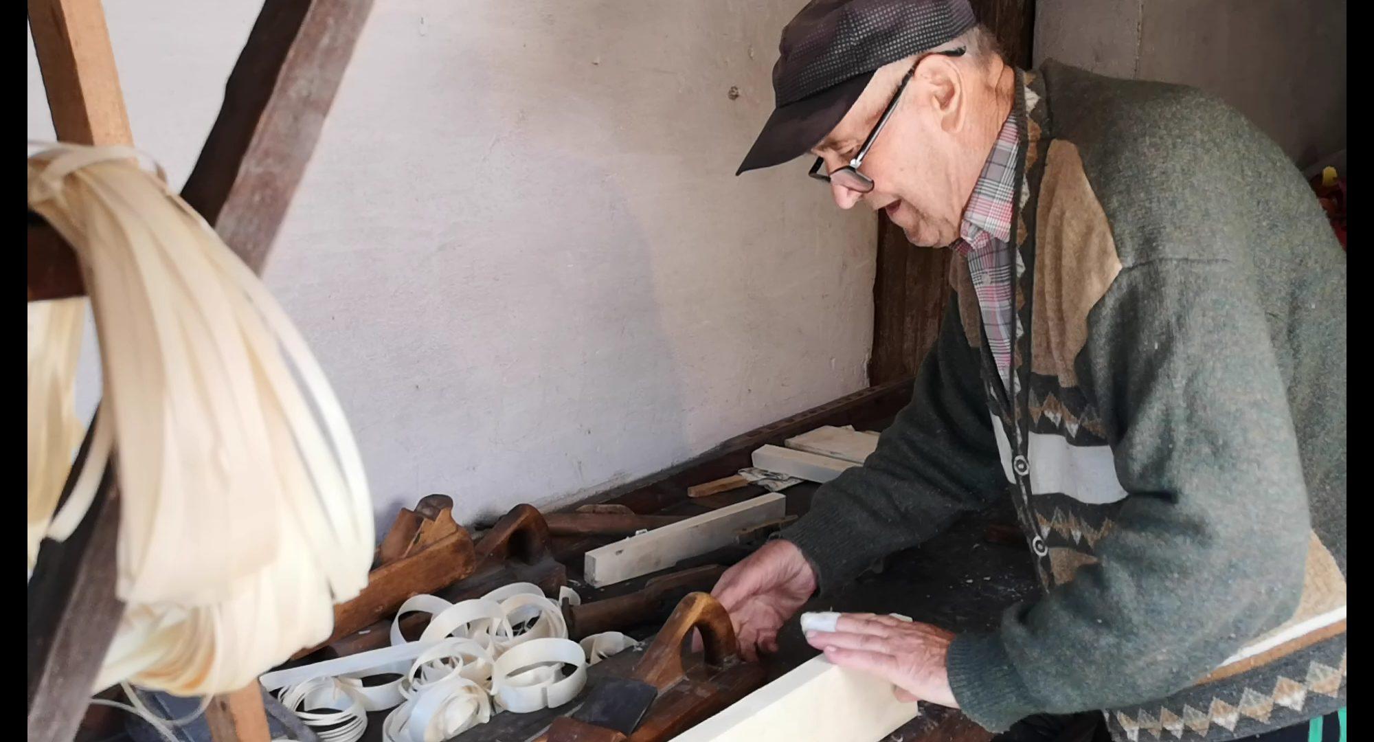Starszy meżczyzna przy warsztacie stolarskim.