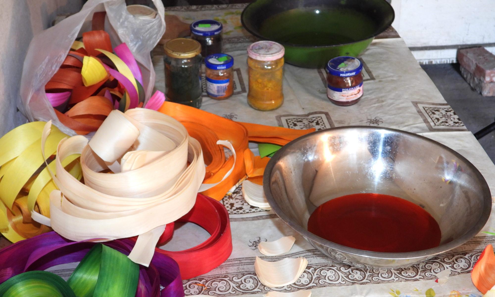 Na zdjeciu barwione wiórki osikowe, miska metalowa z czerwoną farbą, oraz barwniki w proszku w słoikach