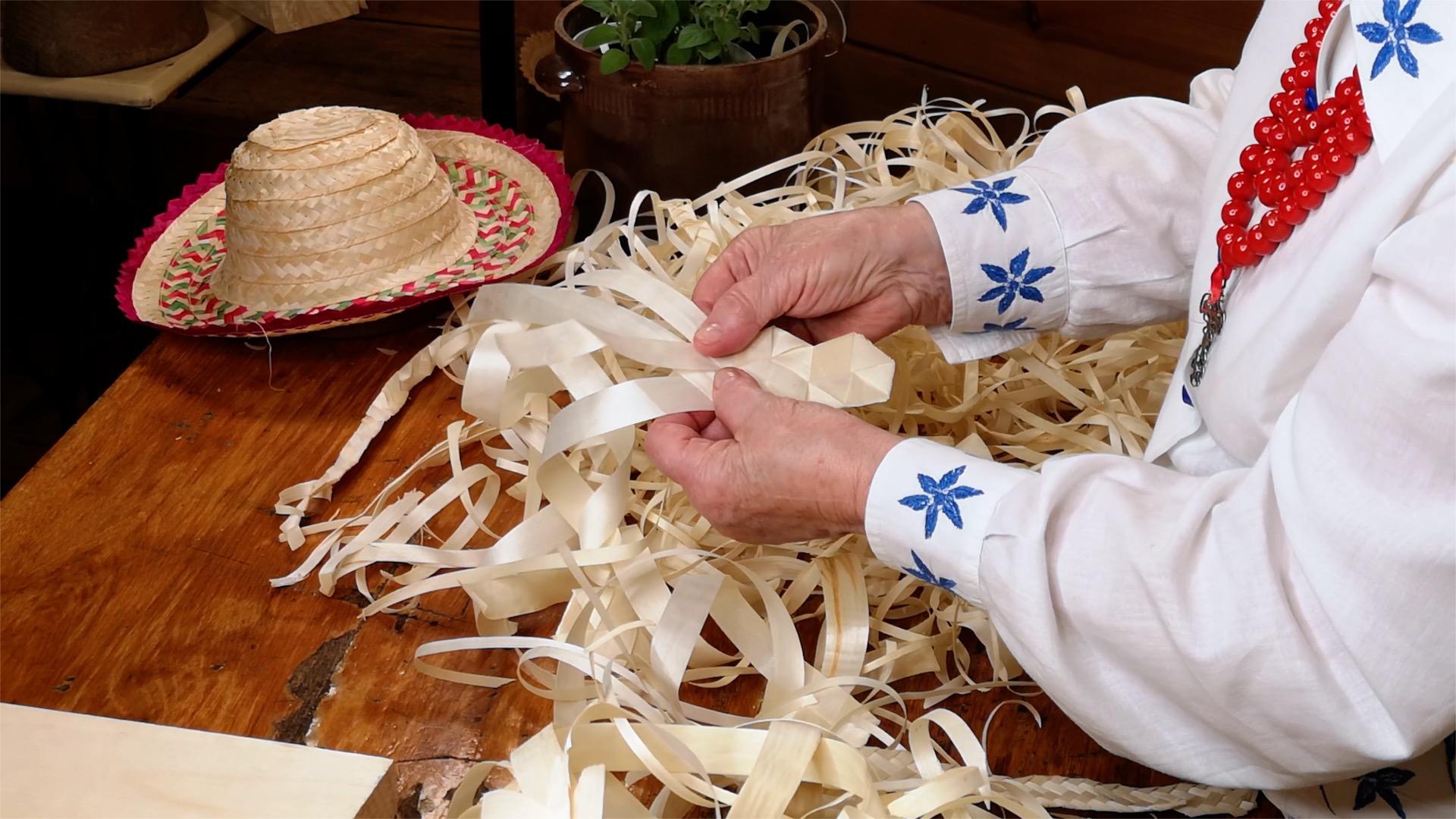 Kobiece dłonie plecące sztuczkę z wiórków osikowych